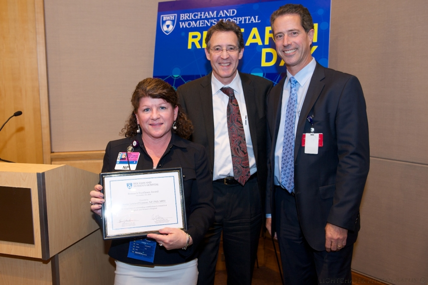 Annie Lewis-O'Connor, PhD, NP, receives a research excellence award at Research Day. Pictured with Brigham Research Institute Director Richard Blumberg, MD, (center) and interim Chief Academic Officer Paul Anderson, MD, PhD.