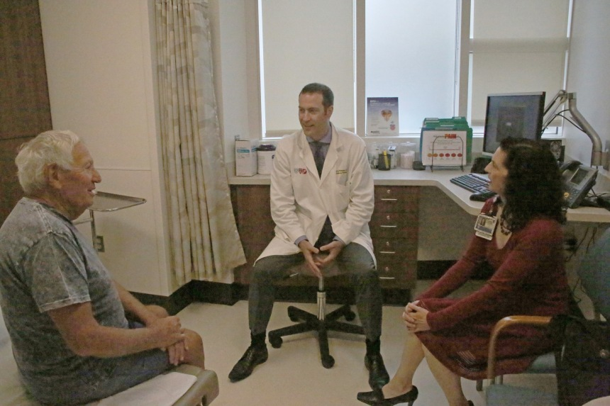 From left: Patient Aleksandr Shiah visits with Mark Preston, MD, urologist, and Veronica Larouche, MA, CMI – Russian, medical interpreter